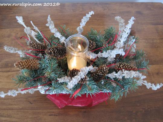 A bread pan, tinfoil, pickin's from a brush pile, ribbon, and a candle make for a lovely centerpiece for only a few dollars.